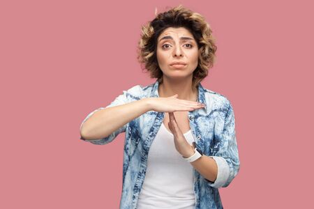 Timeout. I need more time. Portrait of worry pleased young woman with curly hairstyle in casual blue shirt standing with T gesture sign and looking at camera. studio shot, isolated on pink background Archivio Fotografico