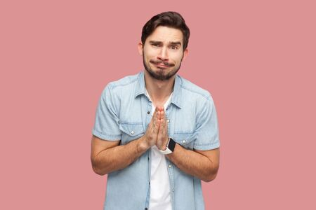 Please help me, or forgive. Portrait of sad hopeful handsome bearded young man in blue casual style shirt standing, looking at camera and begging. indoor studio shot, isolated on pink background. Stock fotó