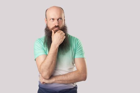 Portrait of confused middle aged bald man with long beard in light green t-shirt standing with hand on chin and looking away and thinking what to do. indoor studio shot, isolated on grey background.