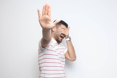 Stop, i dont want to look at this. Portrait of confused bearded young man in striped t-shirt standing, covering his eyes and showing stop gesture. indoor studio shot, isolated on white background. Stock Photo