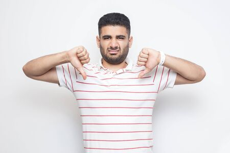 I don't like this. Portrait of displeased bearded young man in striped t-shirt standing with thumbs down dislike sign gesture and looking at camera. indoor studio shot, isolated on white background.