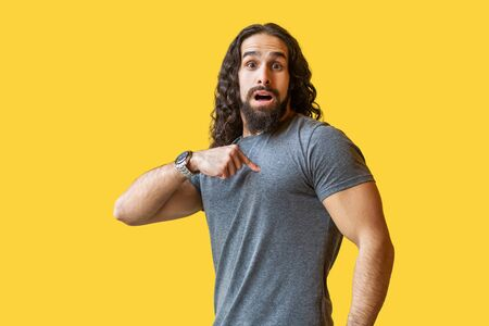Who? me? Portrait of shocked or surprised bearded young man with long curly hair in grey tshirt standing, pointing himself, looking at camera, asking. indoor studio shot isolated on yellow background.
