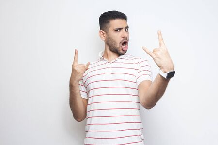 Portrait of funny handsome bearded young man in striped t-shirt standing with rock and roll horns gesture and looking at camaera with surprised face. indoor studio shot, isolated on white background. Фото со стока