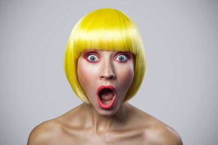 Portrait of surprised cute young woman with freckles, red makeup and yellow wig, looking at camera with amazed wonder face. indoor studio shot, isolated on gray background.