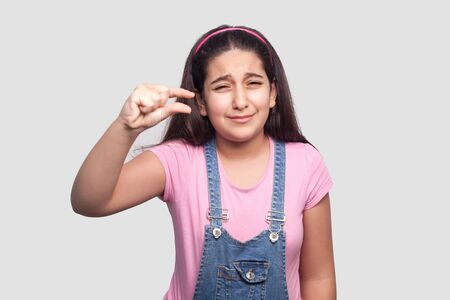 I need few more. Portrait of worry brunette young girl in pink t-shirt and blue overalls standing with small gesture with fingers and looking at camera. indoor studio shot, isolated on gray background Stock Photo