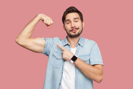 I am strong and I can do anything. Portrait of proud handsome bearded young man in blue casual shirt standing pointing and showing his strong bicep. indoor studio shot, isolated on pink background. Banque d'images - 128122481