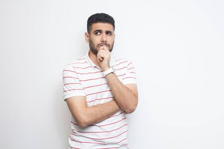 Portrait of thoughtful handsome bearded young man in striped t-shirt standing, looking away and thinking what to do. indoor studio shot, isolated on white background.