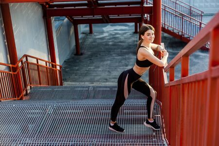 Young happy athletic slim beautiful woman have a rest and standing on stairs after doing cardio interval training in black fashionable sportwear in the street on summer. Outdoor, looking at camera Archivio Fotografico