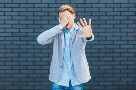 I dont want to look at this. Portrait of ignoring handsome young blonde man in casual style standing, closed his eye and showing stop sign gesture. indoor studio shot on brick wall background. Stock Photo