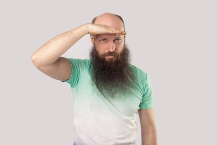 Portrait of attentive middle aged bald man with long beard in light green t-shirt standing with hand on forehead and looking far to find something. indoor studio shot, isolated on grey background.