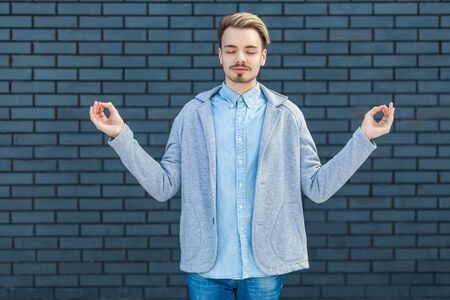 Portrait of calm serious handsome young blonde man in casual style standing in yoga pose, closed eyes and relaxed doing meditation. indoor studio shot on brick wall background. Stock Photo
