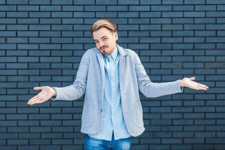 I don't know. Portrait of careless or confused handsome young blonde man in casual style standing with raised arms and looking at camera with doubtful face. indoor studio shot on brick wall background Фото со стока