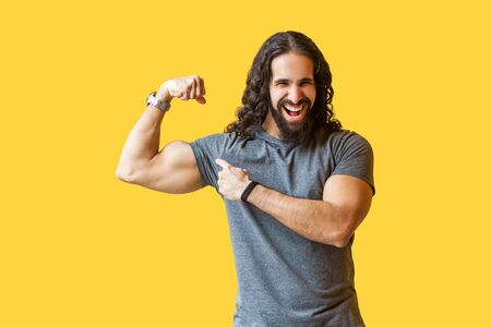 Portrait of funny strong bearded bodybuilder man with long curly hair in grey tshirt standing, pointing at his biceps and looking with toothy smile. indoor studio shot isolated on yellow background. Banque d'images - 128122716