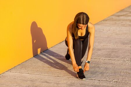 Young attractive sporty woman wearing black sporwear in morning on street standing on knee and preparing for training, tying shoelaces on sneakers, orange wall background, outdoor