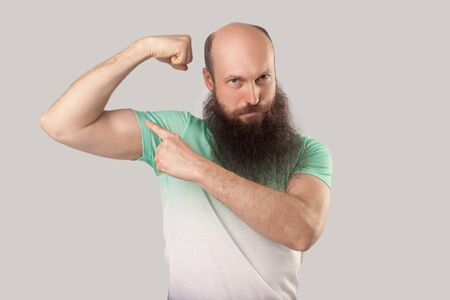 Portrait of serious middle aged bald man with long beard in light green t-shirt standing, pointing his bicep and looking at with haughty face. indoor studio shot, isolated on grey background. Banque d'images - 128123033