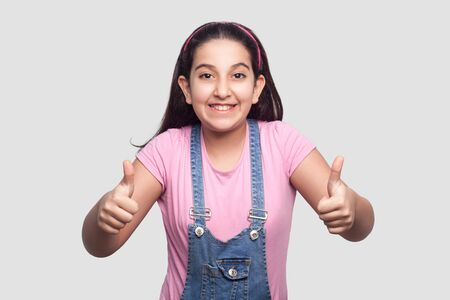 Portrait of satisfied beautiful brunette young girl in casual pink t-shirt, blue denim overalls standing, thumbs up and looking at camera with thumbs up. indoor studio shot isolated on gray background