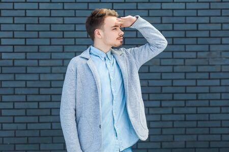 Retrato de hombre rubio joven guapo atento serio en estilo casual de pie con la mano en la frente y mirando a otro lado para encontrar algo. tiro del estudio de interior sobre fondo de pared de ladrillo.