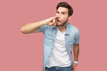 Portrait of crazy handsome bearded young man in blue casual style shirt standing and drilling his nose with funny face. indoor studio shot, isolated on pink background.
