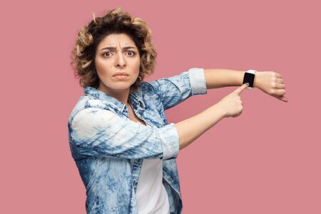 Your time is running out. Portrait of serious bossy young woman with curly hairstyle in casual blue shirt standing and pointing at her smart watch. indoor studio shot, isolated on pink background.