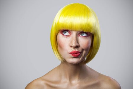 Portrait of pondering cute young woman with freckles, red makeup and yellow wig looking away and thinking about something. indoor studio shot, isolated on gray background.