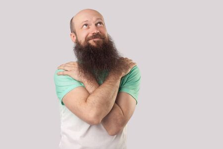 Portrait of smiley, dreamy middle aged bald man with long beard in green t-shirt standing, hugging himself, looking away and dreaming about something. indoor studio shot, isolated on grey background. Stock Photo