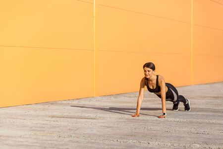 Young happy attractive strong sporty woman wearing black sporwear practicing sport exercises in morning on street, standing on plank position, orange wall background, outdoor