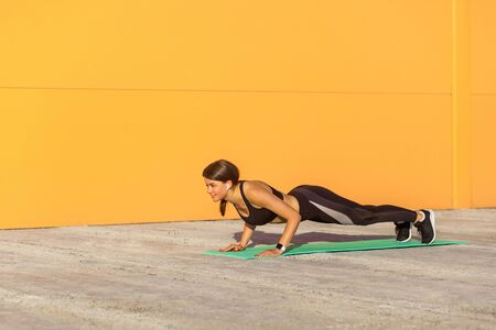 Young woman practicing yoga, doing four limbed staff, push ups or press ups exercise, chaturanga dandasana pose, working out, wearing sportswear, black pants and top. Outdoor, orange wall background