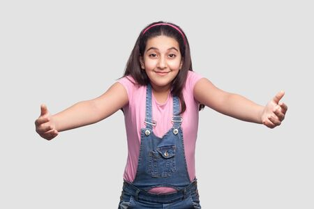 Give me hug. Portrait of happy beautiful brunette young girl in casual pink t-shirt and blue overalls standing, looking with raised arms and want to embrace. studio shot, isolated on gray background. Stock Photo