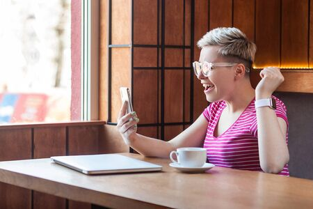 Yes! Side view portrait of happy young surprised blogger with short hair in pink t-shirt is sitting in cafe, holding her smart phone and celebrating her victory and rejoicing . Indoor, lifestyle
