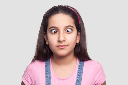 Closeup portrait of crazy funny brunette young girl in casual style, pink t-shirt and blue denim overalls standing with crossed eyes and looking. indoor studio shot, isolated on light gray background.