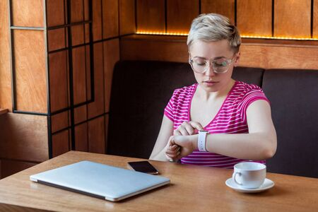 What time is it? Portrait of serious young bussineswoman with short hair in pink t-shirt is sitting in cafe, checking time on wrist smart watch and looking at camera with upset face. Indoor, lifestyle