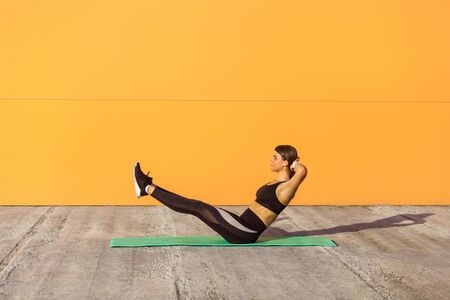 Young sporty attractive woman practicing yoga, doing paripurna navasana exercise, balance pose, working out, wearing sportswear, black pants and top. Outdoor, orange wall background, sport concept