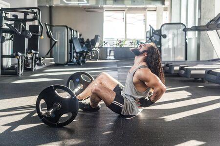 Porträt von Verletzungen junger erwachsener Sportler mit langen lockigen Haaren, die im Fitnessstudio trainieren, auf dem Boden sitzen und starke Rückenprobleme haben, Spasmus schmerzhaft. Mit der Hand in die Wirbelsäule greifen, schreien. Indoor Standard-Bild