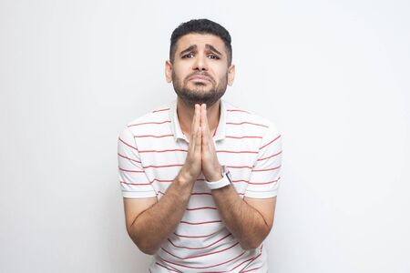 Please help me or forgive. Portrait of sad alone bearded young man in striped t-shirt standing, palm hands and looking at camera pleading or begging. indoor studio shot, isolated on white background.