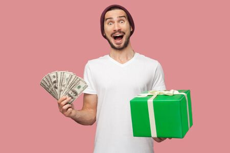 Portrait of suprised handsome bearded young hipster man in white shirt and casual hat standing, holding fan of cash dollars and green present box. Indoor, isolated, studio shot, pink background