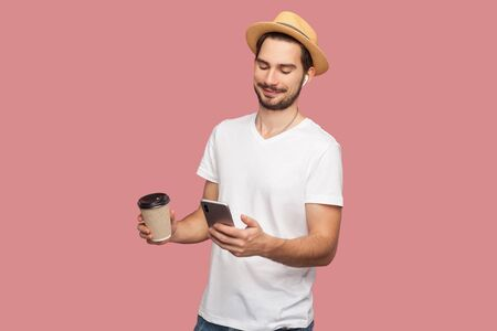 Portrait of satisfied handsome bearded young hipster blogger man in white shirt and casual hat standing with coffee and chatting on the phone. Indoor, isolated, studio shot, pink background