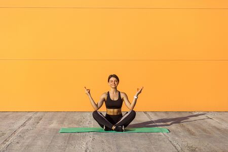 Young sporty attractive woman practicing yoga, doing ardha padmasana exercise, meditating in half lotus pose with mudra gesture, working out, wearing black sportswear. Outdoor, orange wall background,