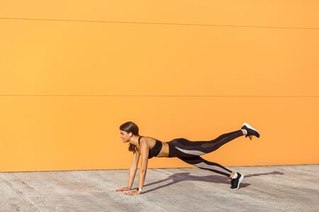 Young satisfied beautiful woman wearing black sporwear practicing sport exercises in morning on street, standing on plank position with raised leg, holding balance, orange wall background, outdoor