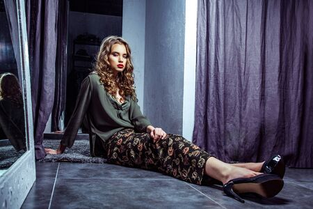 Fashion model with makeup and wavy hairstyle in stylish clothes and high heels shoes sitting on dark gray floor in fitting room and looking at camera with serious face. Indoor studio shot.