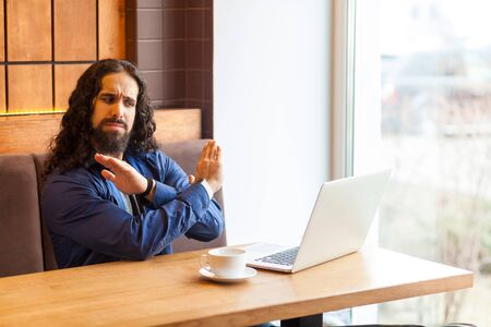 Stop talking! Portrait of angry handsome young adult man freelancer in casual style sitting in cafe and talking with his friend in laptop, showing stop gesture with hands. Indoor, lifestyle concept