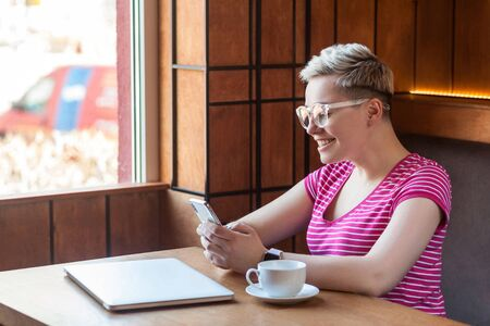 Side view portrait of satisfied happy young blogger with blonde short hair in pink t-shirt is sitting in cafe, holding phone with toothy smile, reading cute message. Indoor, healthy lifestyle Stock Photo