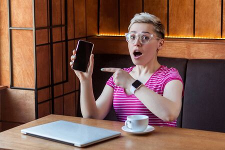 Portrait of beautiful unbelievable young blogger with short hair in pink t-shirt and eyeglasses is sitting in cafe, holding phone and pointing finger, looking at camera with shoked face. Indoor,