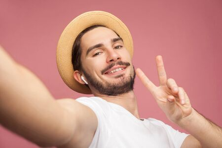 Close up portrait of fashion handsome bearded young hipster blogger in white shirt and casual hat posing and making selfie on phone, showing v sign. Indoor,isolated, studio shot, pink background