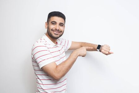Good result and ontime. Happy handsome bearded young man in striped t-shirt standing, showing his smart watch and looking at camera with toothy smile. indoor studio shot, isolated on white background.