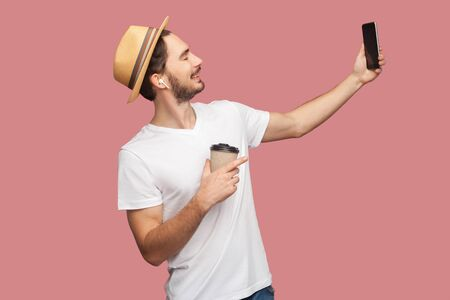 Side view portrait of handsome bearded young hipster man in white shirt and casual hat posing and making selfie photo with smile, blogger lifestyle. Indoor,isolated, studio shot, pink background Stock Photo