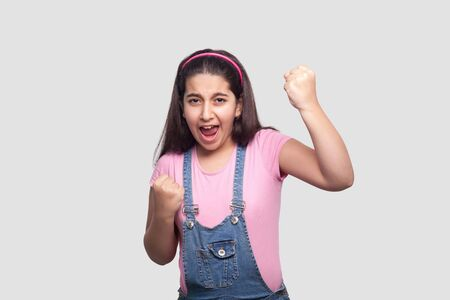 Portrait of rejoicing winner brunette young girl in casual pink t-shirt and blue denim overalls standing, screaming and celebrating her victory. indoor studio shot, isolated on light gray background.