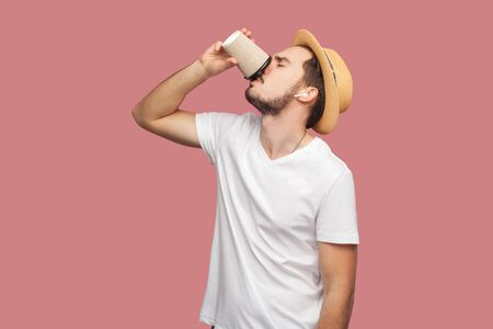 Portrait of handsome bearded young hipster man in white shirt and casual hat standing and drinking coffee in paper cup, freshness lifestyle. Indoor, isolated, studio shot, pink background