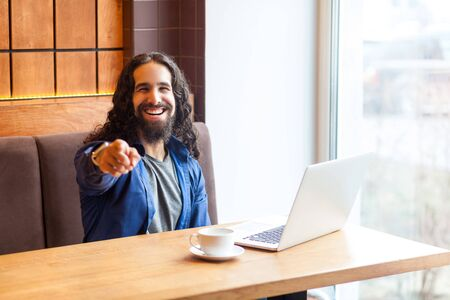 Hey you! Portrait of happy handsome young adult man freelancer in casual style sitting in cafe, pointing finger, looking at camera with toothy smile, bussinessman in office. Indoor, lifestyle concept