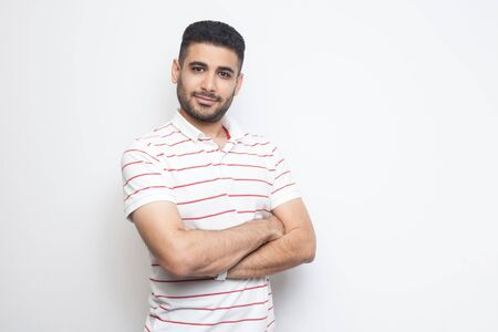 Portrait of happy successful handsome bearded young man in striped t-shirt standing with crossed arms and looking at camera with smile. indoor studio shot, isolated on white background.