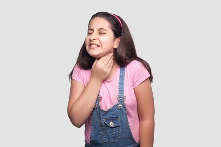 Throat or neck pain. Portrait of sick brunette young girl in pink t-shirt and blue overalls standing and holding her painful neck and feeling bad. indoor studio shot, isolated on light gray background
